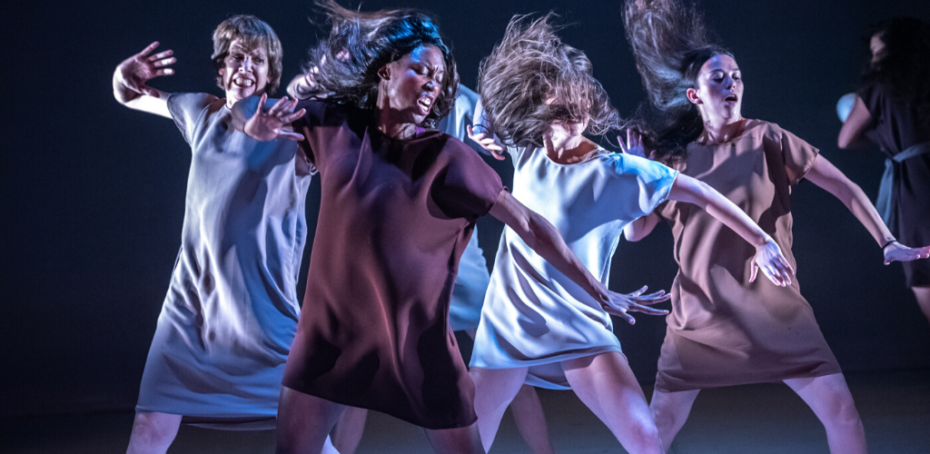 Four women in movement under stage lights.
