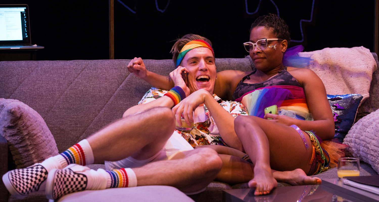 Adrian Shepherd-Gawinski and Monice Peter on the couch wearing rainbow clothing. Stage photo.