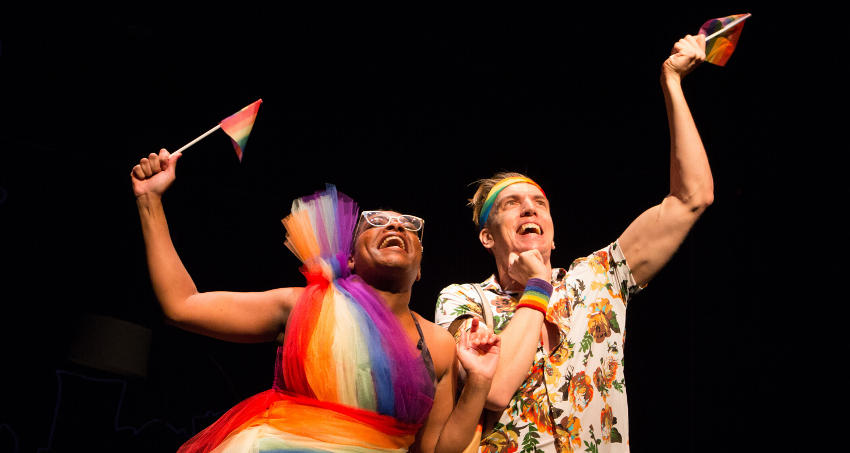 Monice Peter and Adrian Shepherd-Gawinski waving pride flags. Stage photo.