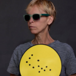 Alex Bulmer holding a yellow sign in Braille.