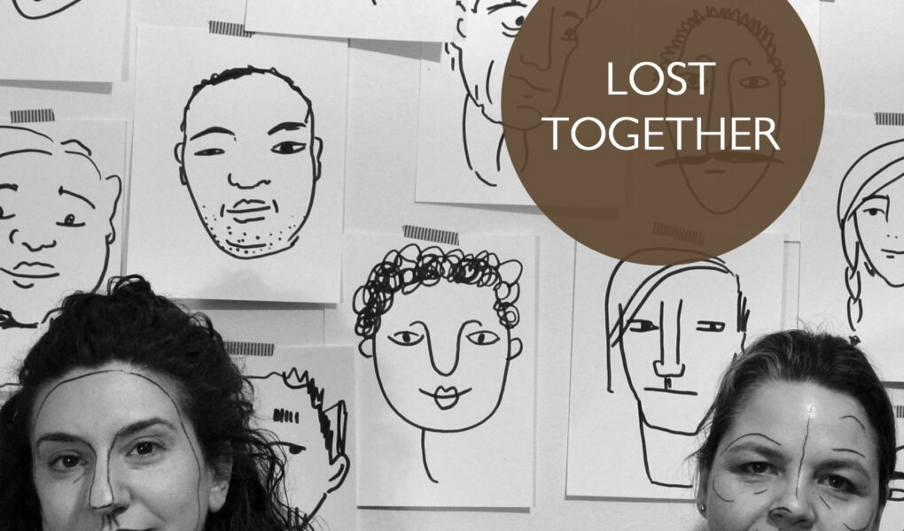 Poster for Lost Together. SHIRA LEUCHTER and MICHAELA WASHBURN stand in front of a wall postered with line drawing of faces. Sheila and Shira have lines drawn on their faces similar to the posters behind them.