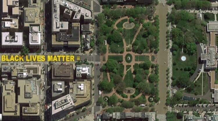 Aerial view of a city and park space, with Black Lives Matter written in yellow on the road.