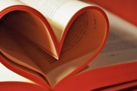 A book with pages curled to make a heart shape.