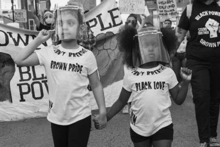 """Black and white image of two children, holding hands and wearing face shields, at a protest. One wears a shirt that says """"Brown pride"""" and the other wears a shirt that says """"Black love."""""""