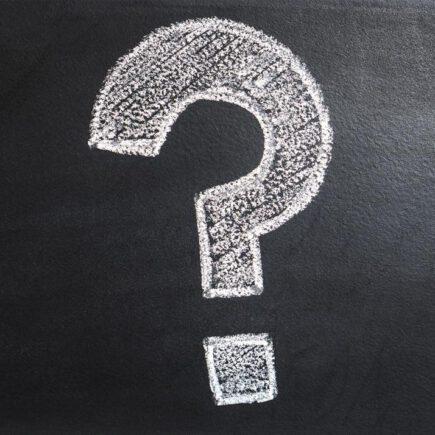 Question mark drawn in chalk on a blackboard.