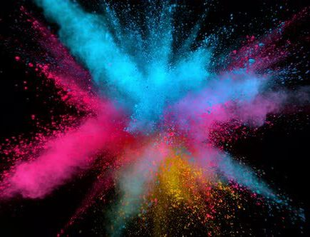 Colourful pigment explodes outwards on a black background.