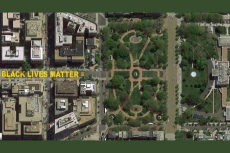 """Aerial view of a city, with """"Black Lives Matter"""" written in yellow paint on the street."""