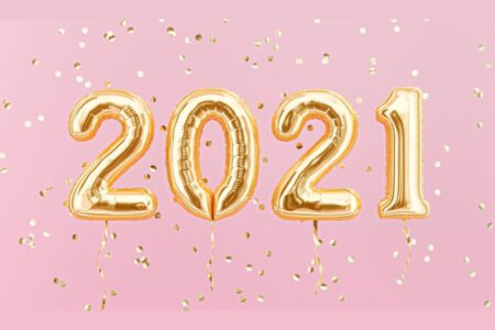 Gold 2021 balloons on a pink background.