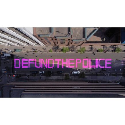 """Aerial view of a street with """"Defund the police"""" painted in pink letters."""