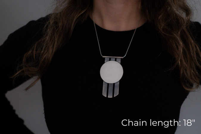 Miranda Britton, the artist, a white woman with brown hair wearing a black shirt, models a necklace that has a circular pendant with three metal spikes going vertically off of the bottom of the circle.
