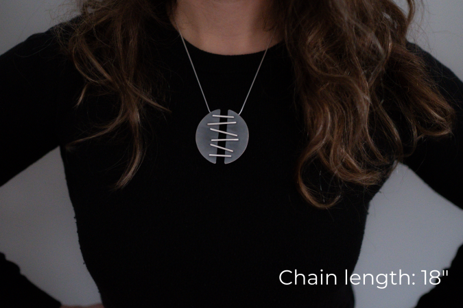 Miranda Britton, the artist, a white woman with brown hair wearing a black shirt, models a necklace that has two half-circle pendants that are connected with metal that is meant to look like stitches, holding the two halves together.