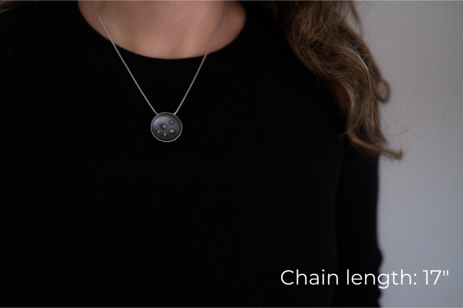 Miranda Britton, a white woman with brown hair wearing a black shirt, models the necklace that she has made. The necklace has a circular pendant with 5 dots in the centre, and is on a grey chain.