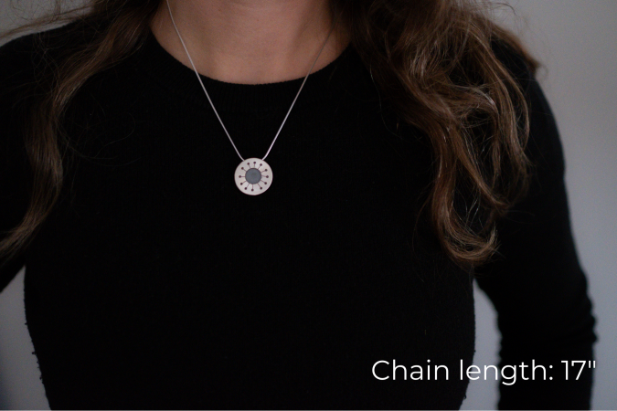 Miranda Britton, the artist, a white woman with brown hair wearing a black shirt, models a necklace that has a circular with a hole in the center, and 12 branches to much smaller holes coming off of the center.