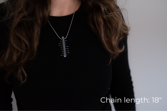 Miranda Britton, the artist, a white woman with brown hair wearing a black shirt, models a necklace that has a rectangle pendant with 8 smaller pieces of metal crossing the center piece.