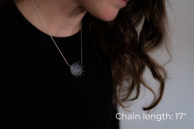 Miranda Britton, the artist, a white woman with brown hair wearing a black shirt, models a necklace that has a circular metal pendant that looks like a pin cushion, with 14 pins sticking out of the pendant.