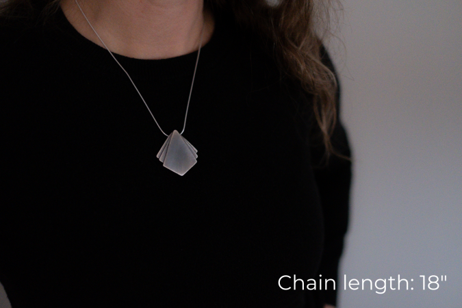 Miranda Britton, the artist, a white woman with brown hair wearing a black shirt, models a necklace that has a diamond shaped pendant at the center with two small triangle shapes on either side of the main pendant.