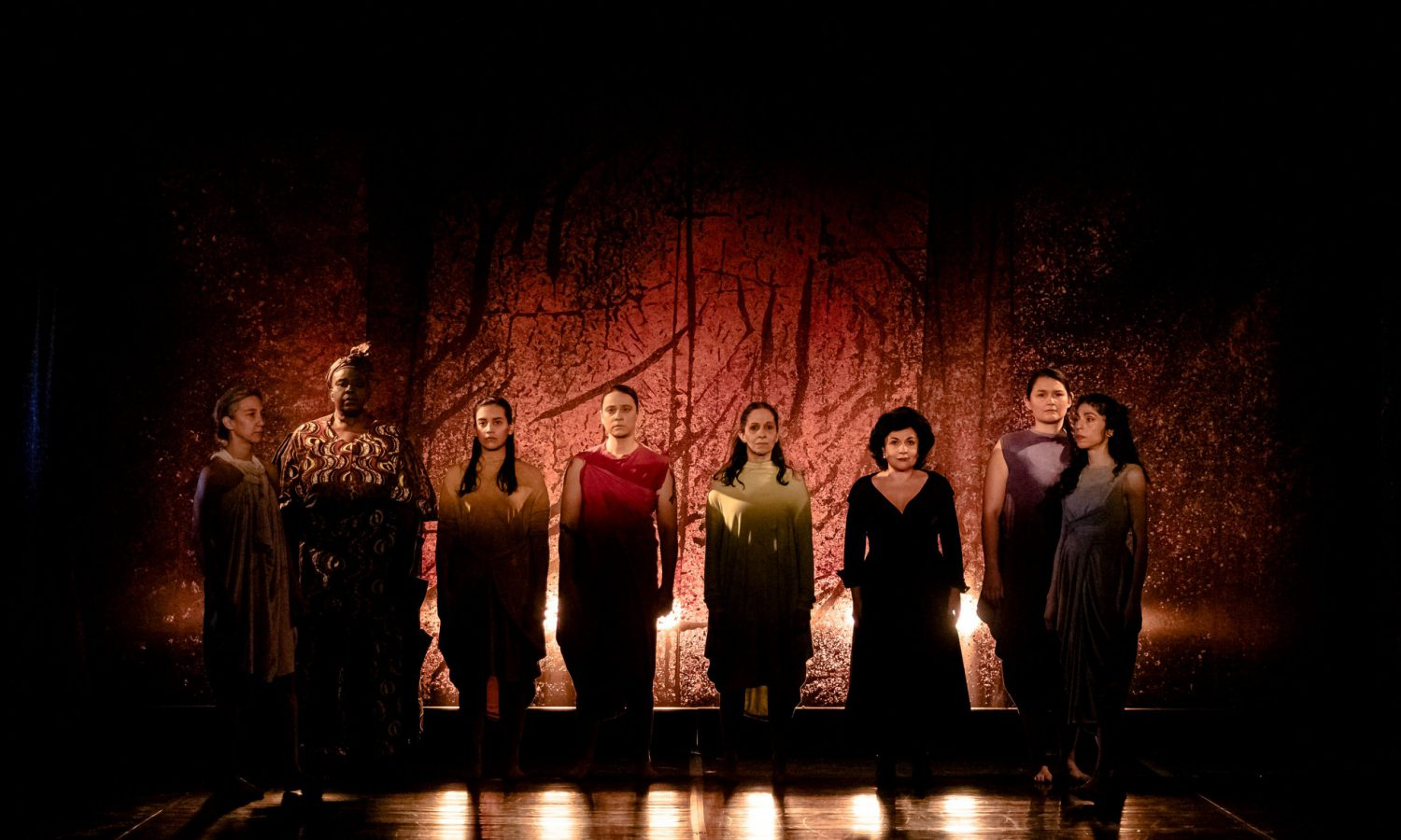 Eight women stand in front of a red backdrop. Stage photo.