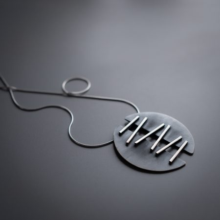 A necklace is lying diagonally on a grey surface. The necklace has two half-circle pendants that are connected with metal that is meant to look like stitches, holding the two halves together.