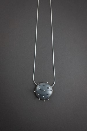 Against a grey background is a necklace that has a circular metal pendant that looks like a pin cushion, with 14 pins sticking out of the pendant.