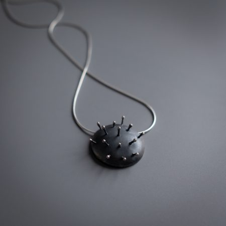 A necklace is lying diagonally on a grey surface. The necklace has a circular metal pendant that looks like a pin cushion, with 14 pins sticking out of the pendant.