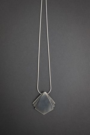 Against a grey background is a necklace that has a diamond shaped pendant at the center with two small triangle shapes on either side of the main pendant.