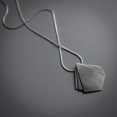 A necklace is lying diagonally on a grey surface. The necklace has a diamond shaped pendant at the center with two small triangle shapes on either side of the main pendant.